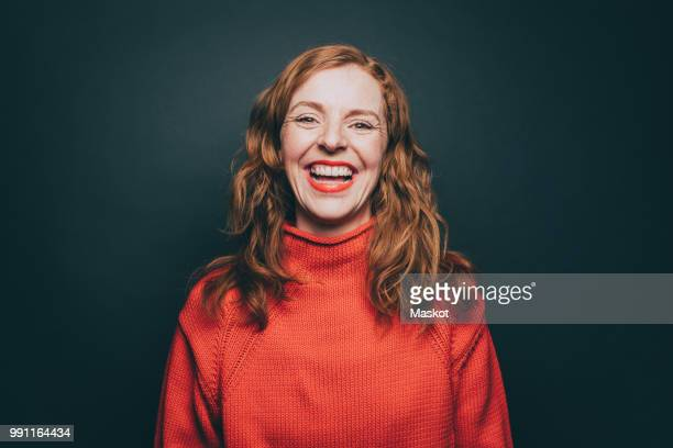 portrait of woman in orange top laughing against gray background - lachen stock-fotos und bilder