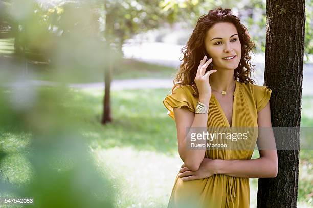 Portrait of woman in park chatting on smartphone