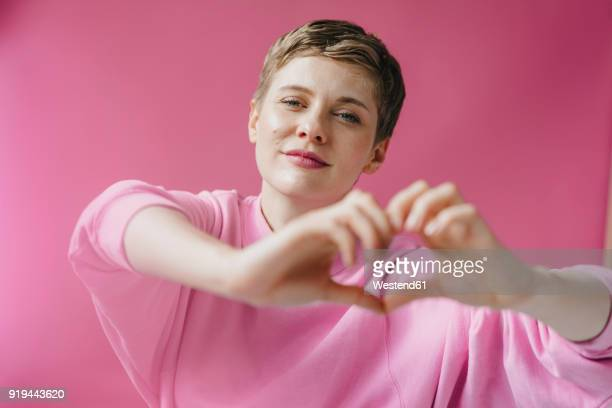 Portrait of woman in pink shaping heart with her hands