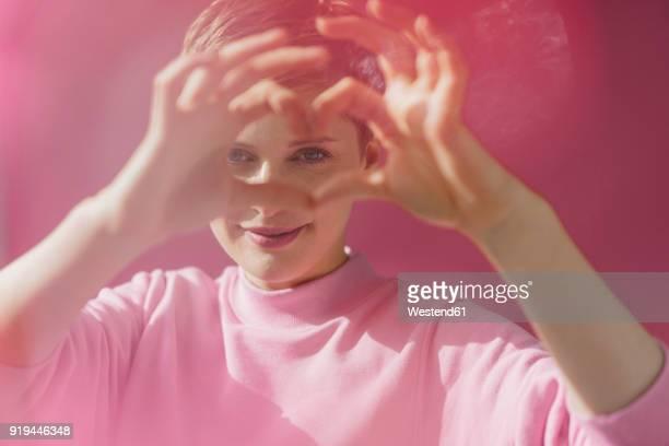 portrait of woman in pink shaping heart with her hands - liebe stock-fotos und bilder