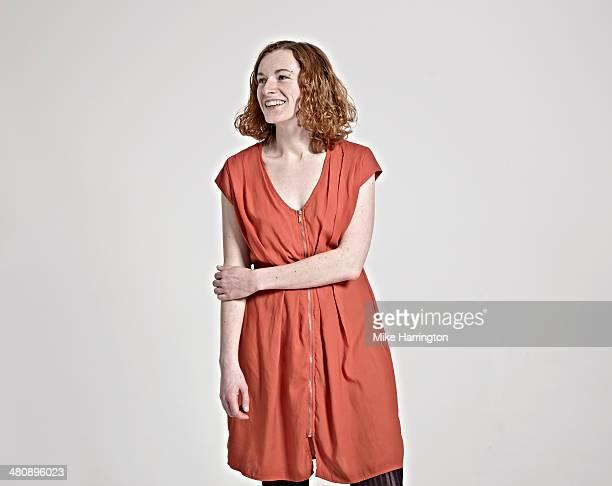 Portrait of woman in red dress smiling sideways.