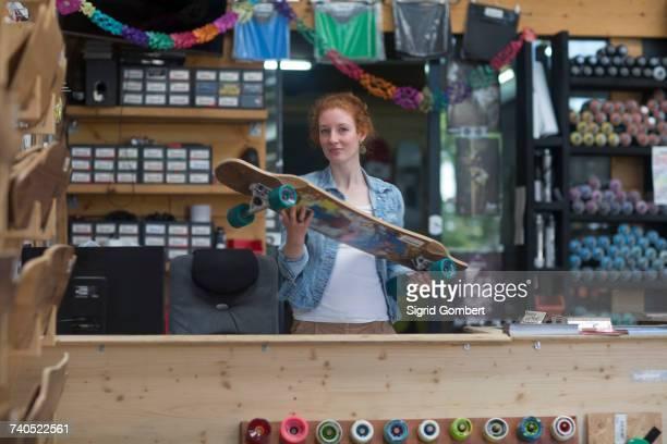 portrait of woman in skateboard shop, holding skateboard - sigrid gombert stock-fotos und bilder