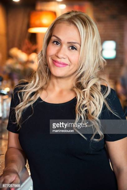 Portrait of woman in smart casual clothes in a bar.