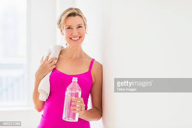 Portrait of woman in sports clothing holding water bottle