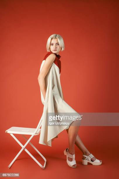 portrait of woman in studio on the red background - multi coloured dress stock pictures, royalty-free photos & images