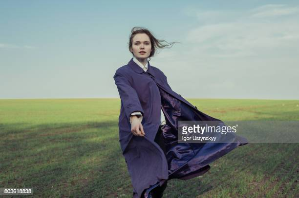 portrait of woman in the field in coat - dark clothes stock photos and pictures