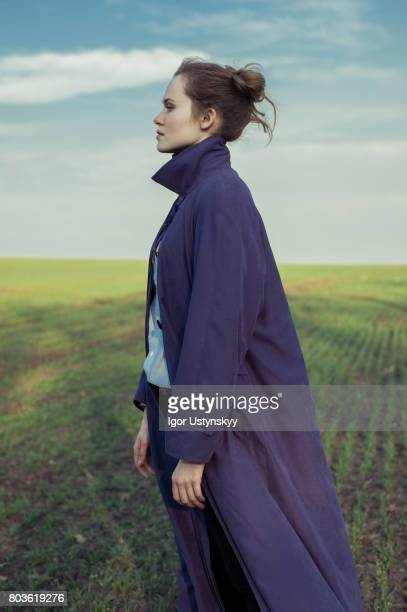 portrait of woman in the field in coat - cover design stock pictures, royalty-free photos & images