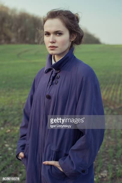 portrait of woman in the field in coat - nature magazine stock pictures, royalty-free photos & images