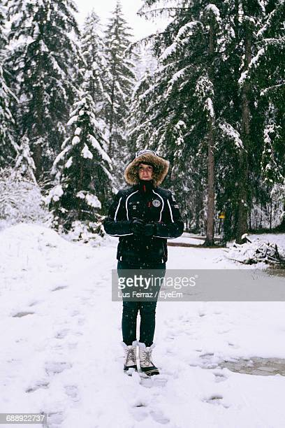 portrait of woman in warm clothes standing on snowfield - snowfield stock pictures, royalty-free photos & images