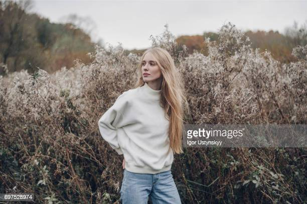 portrait of woman in white sweater near the bushes in autumn - jeune femme blonde photos et images de collection