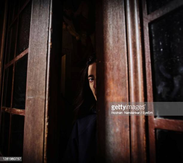 portrait of woman in window - hiding stock pictures, royalty-free photos & images