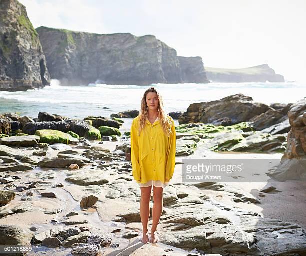 Portrait of woman in yellow raincoat beside sea