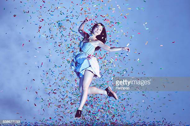 Portrait of woman jumping in confetti
