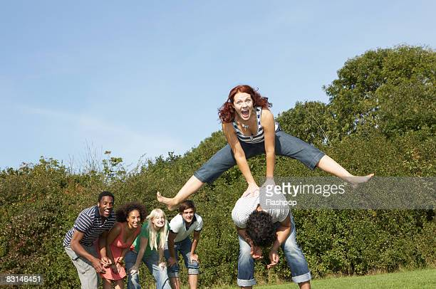 portrait of woman jumping over the top of man - medium group of people stock pictures, royalty-free photos & images