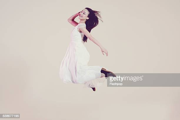 portrait of woman jumping - in de lucht zwevend stockfoto's en -beelden
