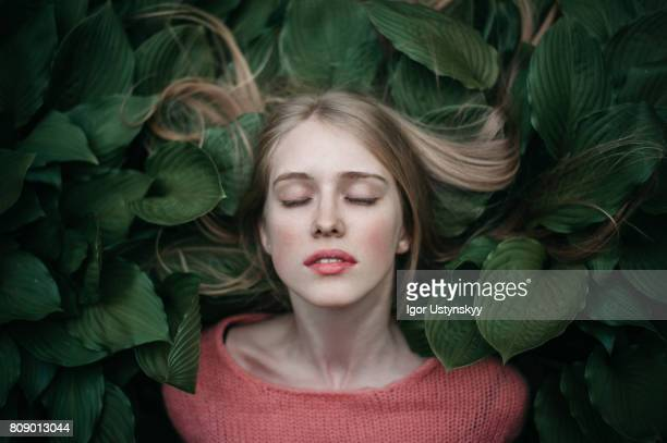 portrait of woman laying on the green leaves - eyes closed stock pictures, royalty-free photos & images