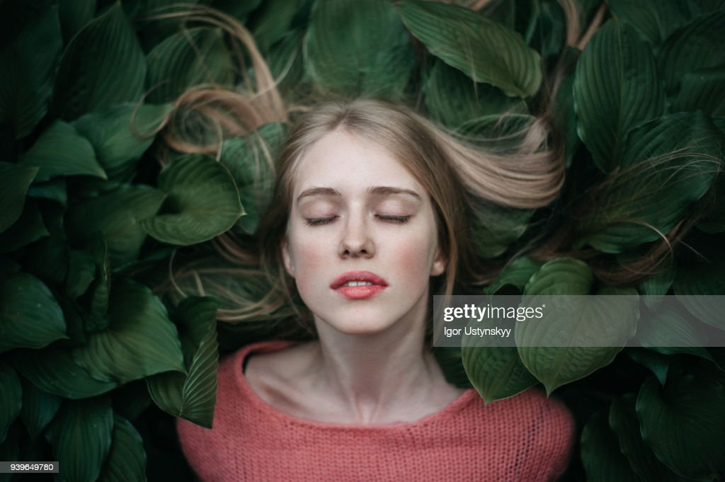 Portrait of woman laying on the green leaves : Foto de stock