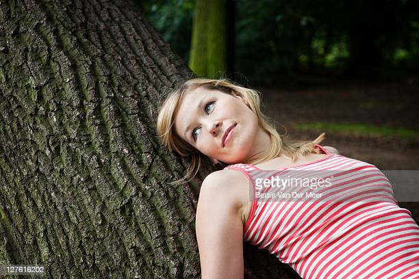 portrait of woman laying on treetrunk.
