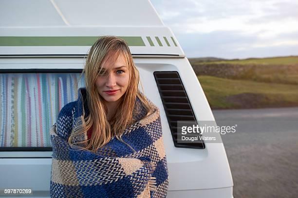 Portrait of woman leaning against camper van.