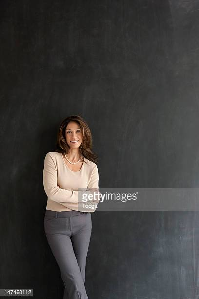 Portrait of woman leaning against gray wall