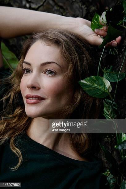 portrait of woman leaning against tree - einzelne frau über 30 stock-fotos und bilder