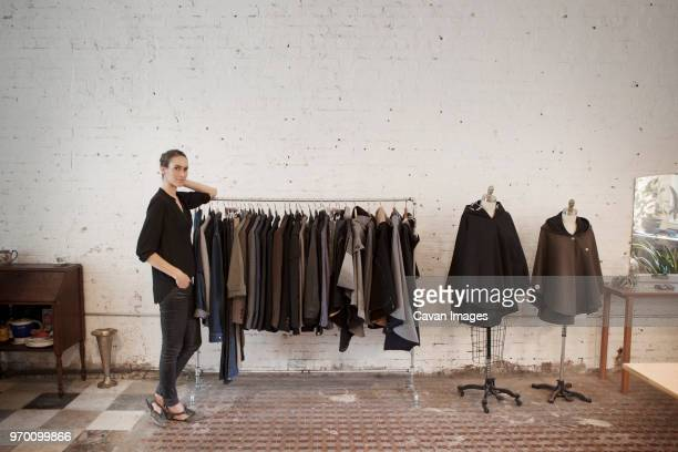 portrait of woman leaning on clothes rack at clothing store - clothes rack stock pictures, royalty-free photos & images