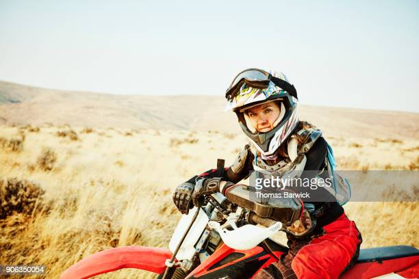Portrait of woman leaning on handlebars of dirt bike during desert ride