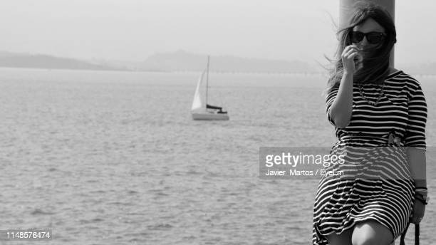 portrait of woman leaning on pole against sea - striped dress stock pictures, royalty-free photos & images