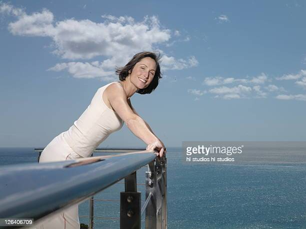 Portrait of woman leaning on railing and smiling