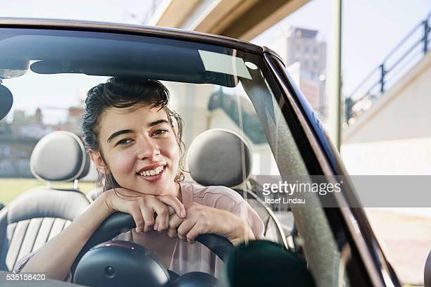 Portrait of woman leaning on steering wheel