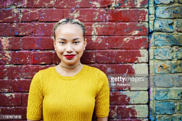portrait of woman looking at camera next to wall - young adult stock pictures, royalty-free photos & images