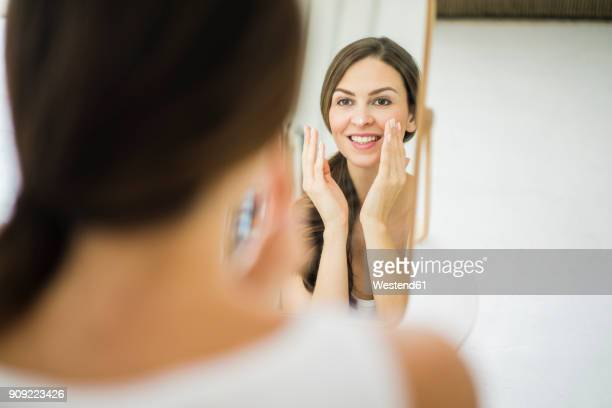 portrait of woman looking at her mirror image in the morning creaming her face - look back at early colour photography stock photos and pictures