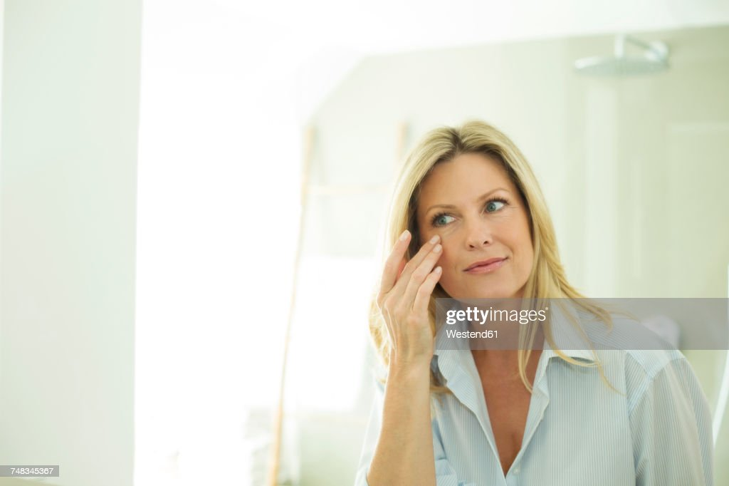 Portrait of woman looking at her mirror image in the morning : Stock Photo