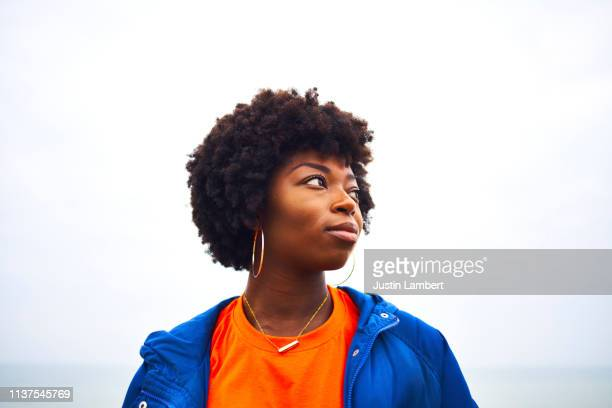 portrait of woman looking off camera with colourful clothing - hipster fotografías e imágenes de stock