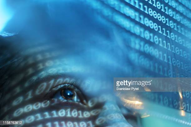 portrait of woman looking on blue screen lit with binary code - data stock pictures, royalty-free photos & images