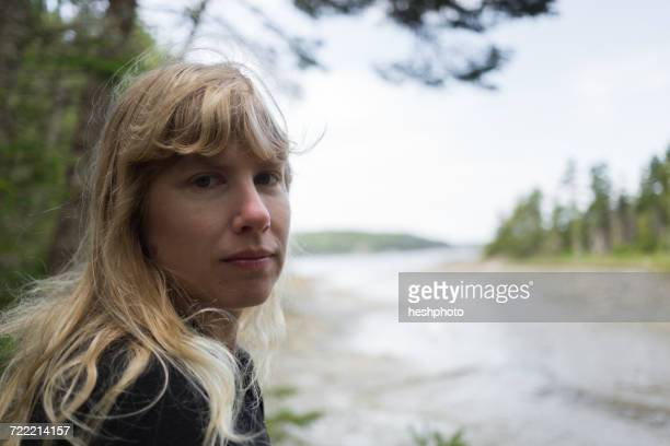 portrait of woman looking over her shoulder at coast of maine, usa - heshphoto stock pictures, royalty-free photos & images