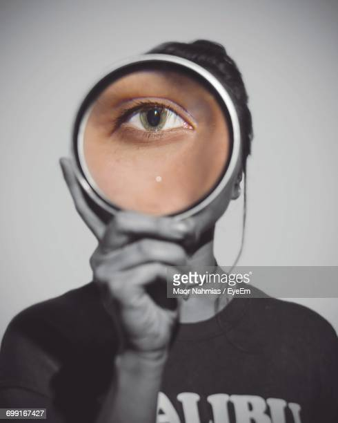 Portrait Of Woman Looking Through Magnifying Glass Against White Background