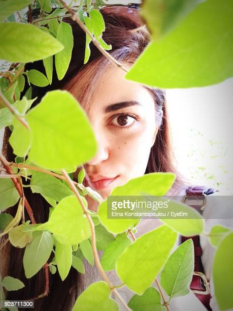 Portrait Of Woman Looking Through Plants