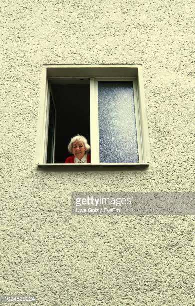 portrait of woman looking through window - fenster stock-fotos und bilder