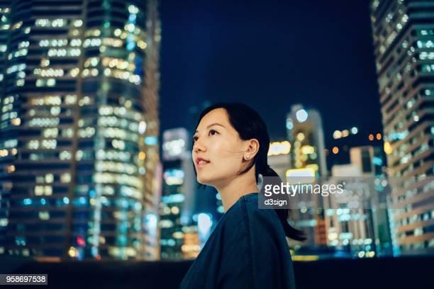 portrait of woman looking up to sky with confidence against city background - werkneemster stockfoto's en -beelden