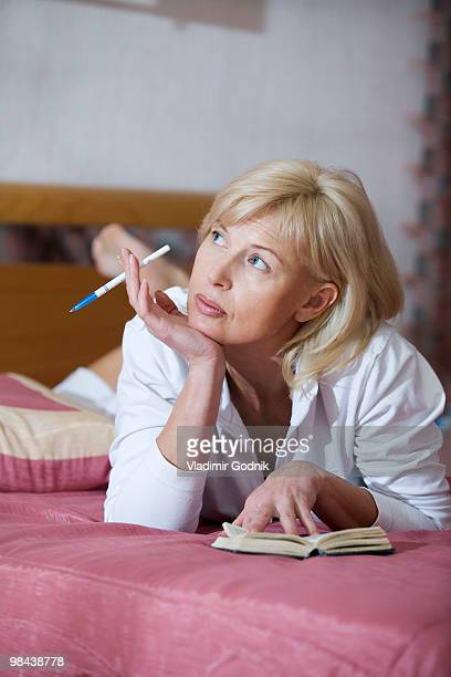 portrait of woman lying on bed looking at diary