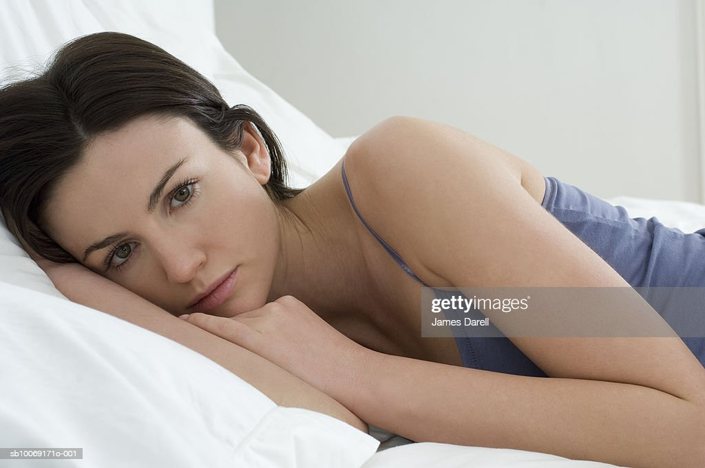 Portrait of woman lying on bed : Stockfoto
