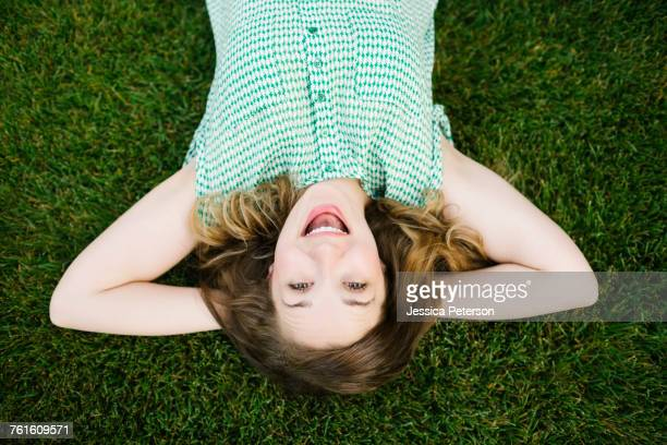 portrait of woman lying on grass and laughing - short sleeved stock pictures, royalty-free photos & images