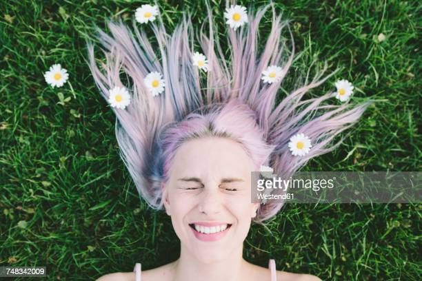 Portrait of woman lying on grass with eyes closed and daisies on hair