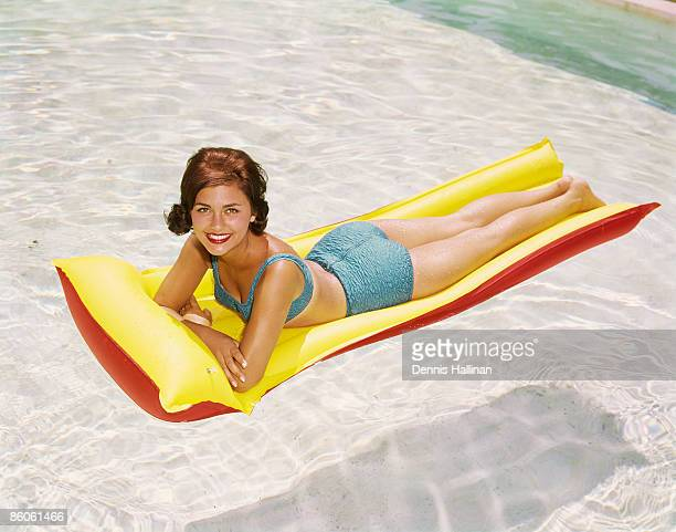 Portrait of woman lying on raft in swimming pool