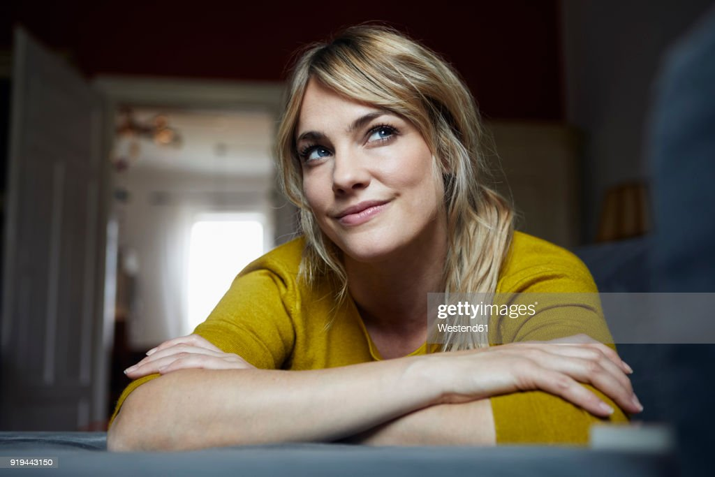 Portrait of woman lying on the couch at home thinking : Stock-Foto