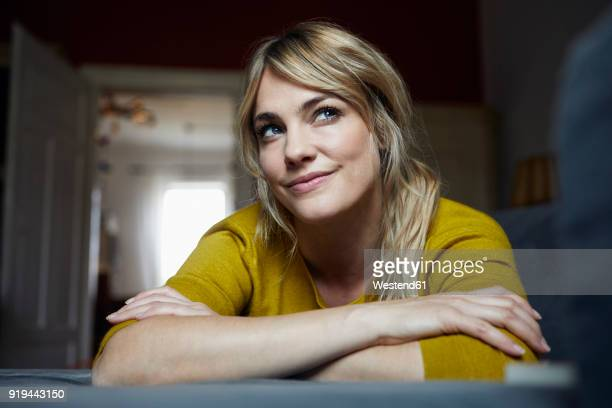 portrait of woman lying on the couch at home thinking - smiling stock-fotos und bilder
