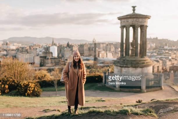 portrait of woman near historic monument, calton hill, edinburgh, scotland - tourist stock pictures, royalty-free photos & images
