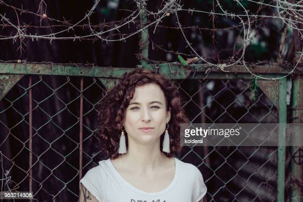 portrait of woman next to barbed wire - 30 39 años fotografías e imágenes de stock