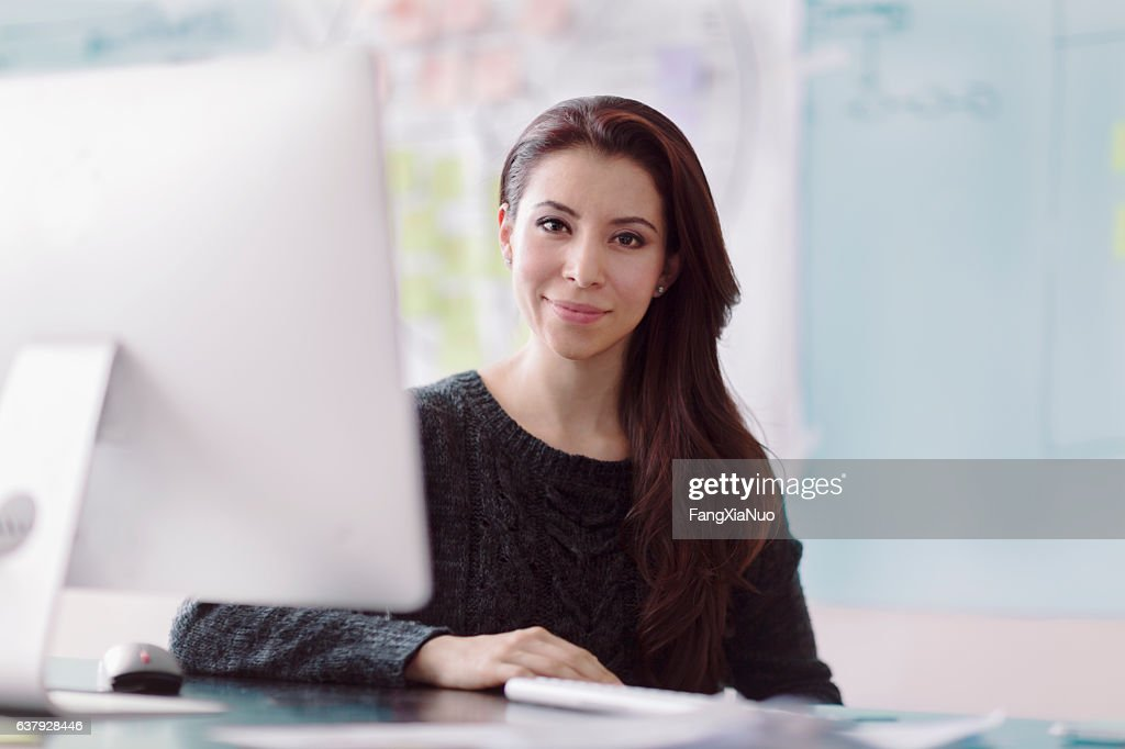 Portrait of woman next to computer in studio office : Stock Photo